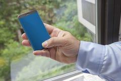 Vorstadtmann, der ein simsendes Baby des Smartphone ein Fenster mit gr?nen Baumbl?ttern im Hintergrund h?lt lizenzfreies stockfoto