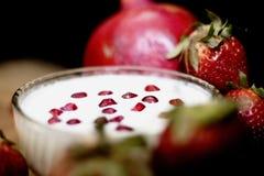 Vorstehende Fruchtcreme auf hölzernem Brett mit Granatapfel und anderen Erdbeeren in einem dunklen Hintergrund stockfotografie