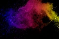 Vorstmotie van gekleurde die poederexplosie op zwarte achtergrond wordt geïsoleerd De samenvatting van Veelkleurig stof splatted stock afbeelding