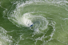 Vortex, eddy or whirlpool with foam. Vortex or whirlpool with foam in the river made by turning ship giving a light green color to the water Stock Photos