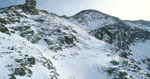 Vorwärtsantenne über schneebedecktem Berg des Winters mit den Bergsteigenskifahrerleuten, die herauf das Klettern gehen Schnee de stock video