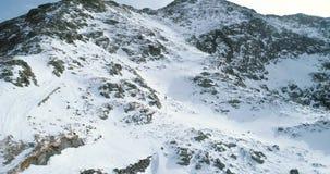 Vorwärtsantenne über schneebedecktem Berg des Winters mit den Bergsteigenskifahrerleuten, die herauf das Klettern gehen Schnee de stock video footage