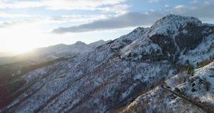 Vorwärtsvon der luftdraufsicht entlang Straße auf weißem Schneeberg im Winter Forest Woods Snowy-Gebirgsstraßen-Weg establisher stock footage