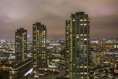 Vorwerk und Stadt afrer Dunkelheit Stockbild