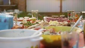 Vorzüglich verzierte Tabelle mit köstlichem Fleisch, Salaten und Wein für romantisches Abendessen im Dorf im Freien herein stock video