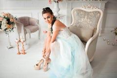 Vorzügliche Brautkleider von Hochzeitsschuhen im Hintergrund des eleganten Innenraums mit Kerzen und Blumen stockfotos