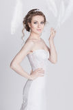 Vorzügliche junge und träumerische Braut in einem luxuriösen Spitzehochzeitskleid Lizenzfreies Stockfoto