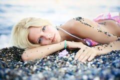 Vorzügliche schöne blonde Frau liegt auf dem Strand von den sonnigen Kieseln leicht und hell auf einer Meerkreuzfahrt, einer Erho Lizenzfreie Stockfotografie