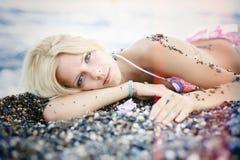 Vorzügliche schöne blonde Frau liegt auf dem Strand von den sonnigen Kieseln leicht und hell auf einer Meerkreuzfahrt, einer Erho Lizenzfreie Stockbilder