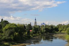 Voskresensky Cathedral among green trees against the blue sky, the city of Kashin, Tver region. The Voskresensky Cathedral among the summer green trees, near the stock photo