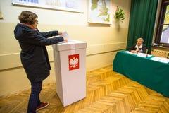 Votante en el colegio electoral durante elecciones parlamentarias polacas al Sejm y al senado Imágenes de archivo libres de regalías