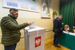 Votante en el colegio electoral durante elecciones parlamentarias polacas al Sejm y al senado Foto de archivo