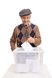 Votante maduro que pone una votación en una caja de votación Imagen de archivo