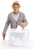 Votante mayor que pone una votación en una caja de votación Imágenes de archivo libres de regalías