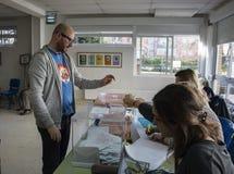 Votante que introduce el sobre dentro de la urna en el colegio electoral para las elecciones generales españolas en Madrid, Españ Fotografía de archivo