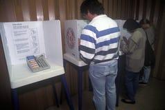 Votantes y cabinas de votación en un colegio electoral Fotos de archivo