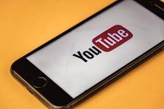 votary Rosja - mogą 03, 2019: Brandnew Jabłczany iPhone 7 z logo YouTube na pomarańczowym tle, YouTube jest popularny zdjęcie stock