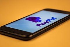 votary Rosja - mog? 5, 2019: Paypal logo na smartphone ekranie na pomara?czowym tle Paypal jest Ameryka?skim onlinym zap?at? i obrazy royalty free