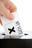 Vote. A hand placing a voting slip into a ballot box over a white background royalty free stock photo