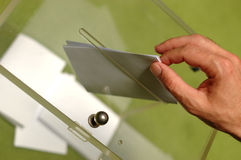 Vote. Hand putting a blank ballot inside the box, elections concept Royalty Free Stock Images