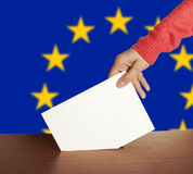 Vote. Hand with ballot and box isolated on Flag of Europe Stock Photo