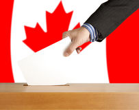 Vote. Hand with ballot and box on Flag of Canada Stock Images