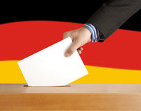 Vote. Hand with ballot and box on Flag of Germany Royalty Free Stock Image