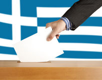 Vote. Hand with ballot and box on Flag of Greece Royalty Free Stock Photography
