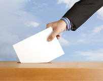 Vote. Hand with ballot and box on sky Royalty Free Stock Images