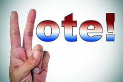 Vote!. A man hand making the V sign to complete the sentence vote! written with the colors of the american flag Stock Image