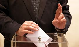 Vote. Hand putting a blank ballot inside the box, elections concept Stock Photography