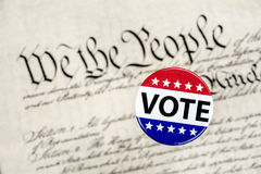 Vote badge and constitution. A vote badge hovers above the constitution as a symbol of an American citizen`s constitutional right to vote Royalty Free Stock Photos