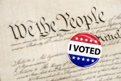 Vote badge and constitution. A vote badge hovers above the constitution as a symbol of an American citizen`s constitutional right to vote Stock Image