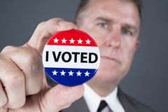Vote badge. A man who voted holds up his voting badge lapel pin Stock Photography