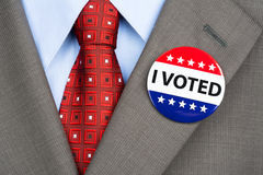 Vote badge on tan suit. A businessman in a tan suit wearing his vote pin on his jacket lapel Royalty Free Stock Photo
