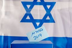 Vote box. Hebrew text Elections 2019 on voting paper over Israel flag background. Israeli legislative Elections for the 21st Knesset Israel 9 April 2019 stock photos