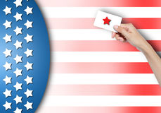 Vote card in hand. Hand holding vote card over USA flag background Royalty Free Stock Photos
