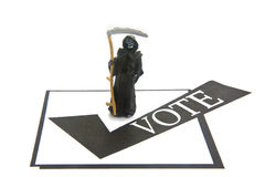 Vote or die. Miniature Death figure with voting box Royalty Free Stock Photo