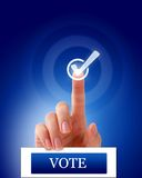 Vote finger check mark. Finger pointing to a check mark over a Vote sign. Blue background royalty free stock photo