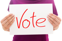 Vote. Girl holding white paper sheet with text Vote stock image
