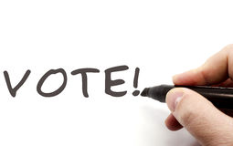 Vote! Hand Writing. A hand with a black felt pen writing the word VOTE! making a great election concept Royalty Free Stock Photos