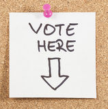 Vote here post. On wooden background Royalty Free Stock Images