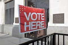 A `Vote Here` sign at the entrance of Lake County Board of Elections in Painesville, Ohio, USA. A `Vote Here` banner is posted across from the entrance to the royalty free stock image