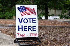 Vote here sign for primaries and elections. Sign for polling location to vote for elected government officials royalty free stock images