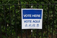 Vote Here. A sign that reads `Vote here` in English, Spanish and Chinese, outside a voting booth in New York City Stock Image