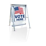Vote here signage. A metal 'Vote Here' sign with the American flag isolated on a white background with a slight shadow royalty free stock photo