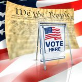 Vote here signage. A metal 'Vote Here' sign with the American flag with 'We the People' and a flag in the background royalty free stock image