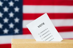Vote inserted into ballot box slot on election. Voting and civil rights concept - vote inserted into ballot box slot on election over american flag Royalty Free Stock Photos