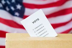 Vote inserted into ballot box slot on election. Voting and civil rights concept - vote inserted into ballot box slot on election over american flag Stock Photo