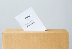 Vote inserted into ballot box slot on election. Voting and civil rights concept - vote with two candidates inserted into ballot box slot on election Stock Image